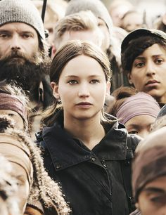 This shot is amazing. She's isn't trying to be anyone else or stand out in a crowd. She's just a Seam girl from District 12. No glitz, glam, or Capitol interference. Just Katniss standing in and with the masses. She is the Mockingjay, but she's the Mockingjay with and for her fellow Panem citizens.