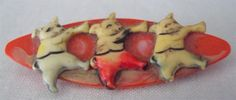 """The Three Little Pigs Antique 1920's brooch or pin. 1 3/4"""" wide x 5/8"""" tall. The red base looks to me like a painted celluloid as do the 3 pigs. Some of the paint has faded or worn off over time. It also appears that the pig on the right has a manufacturer's flawed foot. 