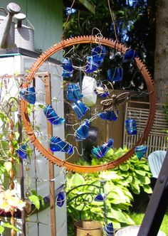 this is made out of an old engine gear, wire  broken blue glass....rusty garden dream catcher :)
