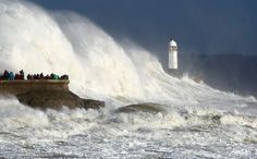 """Huge waves strike the harbor wall and lighthouse at Porthcawl, South Wales, on October 16, 2017, as Storm Ophelia hit the UK and Ireland. Ireland was hit by the """"unprecedented storm"""" on Monday that left two people dead, 120,000 homes and businesses without power and closed every school in the country."""