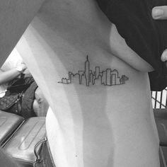 New York skyline tattoo on the right side. Tattoo artist: Jon...