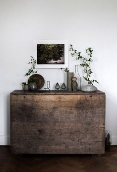 a simply styled zen foyer with wood, pottery, plants and artwork