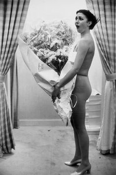 Backstage at Nina Ricci by  Eve Arnold 1977. Model in her underwear at the Nina Ricci show. She is holding a large bunch of flowers the staff have given her after 10 years with Nina Ricci. She is the girl who always wears the bridal gown.