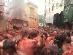 Una multitud de personas se unen en una plaza publica para participar en la Tomatina.