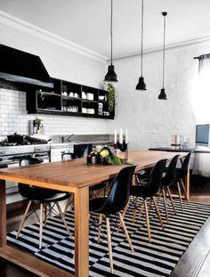 Tipo industrial, o ponto central desta cozinha é a grande mesa de madeira, que acomoda 10 pessoas. As luminárias tipo pêndulo e o tapete listrado ornam com as cadeiras pretas.