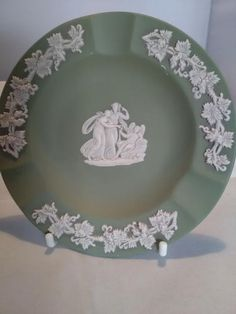 A lovely collectable ash tray from Wedgwood. This is in the sage green jasperware ware with white figures. It has three figures in the centre and an ivy leaf border. It measures 11 centimetres across and is in lovely condition. Toast Rack, Leaf Border, Ivy Leaf, Flower Spray, Wedgwood, Small Flowers, Pale Pink, Ash, Decorative Plates