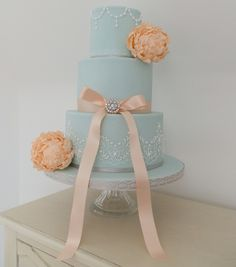 The Ivory Owl Cake Company. Three tier duck egg blue wedding cake. Peach peonies lace work piping bow brooch.
