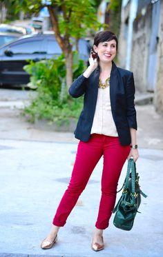 camisa sem mangas creme na frente e preta atrás, blazer preto, calça vermelho escuro, sapatilha de bico fino dourada, bolsa de couro verde, colar de murano dourado e bronze