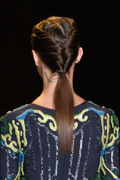 At Herve Leger, the models walked the runway with double-sided French twists that led into a super-low pony and were secured at the nape of their necks with a thin elastic. To get the look, part your hair down the center and work with one side of hair at a time, working it toward the back of your head and then twisting it into itself to create the French twist. Secure with bobby pins and repeat on the opposite side. Lastly, be sure to use a flat iron so the tail lies smoothly from the bottom…