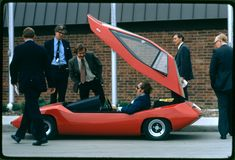 """""""Exhibit at the first symposium on low pollution power systems development held at the Marriott Motor Inn, Ann Arbor. Vehicles and hardware were assembled at the EPA Ann Arbor Laboratory. Part of the exhibit was held in the motel parking lot. Participants looking over the ESB """"Sundancers,"""" an experimental electric car. Ann Arbor, Michigan, October 1973. (Frank Lodge/National Archives/Records of the Environmental Protection Agency)"""""""