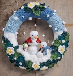 Winter Wreath Crochet a charming scene of snow mommy and her two children having a blast in the freshly fallen snow between beautiful Hellebores flowers and Holly and Ivy leaves. A beautiful, very detailed pattern to create your own winter wreath. Crochet Christmas Wreath, Crochet Wreath, Crochet Snowman, Crochet Christmas Decorations, Christmas Crochet Patterns, Holiday Crochet, Xmas Wreaths, Christmas Knitting, Christmas Crafts