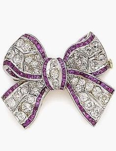 A ruby and diamond bow brooch, circa 1910 Designed as a finely pierced tied ribbon, set throughout with cushion-shaped diamonds, flanked by calibré-cut ruby borders, diamonds approx. 1.85cts total, some rubies deficient, later pin fitting, length 3.0cm
