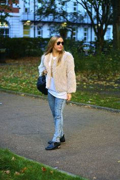 Shop this look on Lookastic:  http://lookastic.com/women/looks/sunglasses-crew-neck-t-shirt-skinny-jeans-necklace-chelsea-boots-backpack-coat/6794  — Black and Gold Sunglasses  — White Crew-neck T-shirt  — Blue Acid Skinny Jeans  — Gold Beaded Necklace  — Black Leather Chelsea Boots  — Black Leather Backpack  — Beige Textured Coat