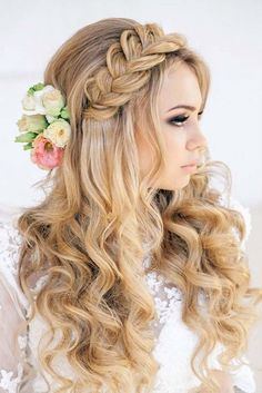 Braided crown with floral hair accessories and tight curls for a modern bride.