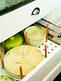 Dish Storage in a Drawer: Store dishes down low to save on cabinet space. Notice adjustable pegs.