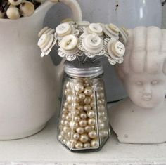 Beads in an old salt shaker, with newspaper and button flowers. Recycle/Repurpose/Upcycle
