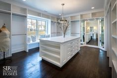 Gorgeous boutique style large walk in closet boasts a gorgeous white modular closet system complete with a window seat framed by floor to ceiling built-in clothes rails topped with open cubbies, a full length 3-way mirror, and a stunning island featuring display shelves and drawers topped with gray and white marble countertops lit by a drum pendant light, Hudson Valley Lighting Middlebury 3 Light Drum Pendant.