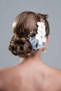 Peinado de novia recogido formado por una trenza que termina en un moño bajo y con un tocado de flores