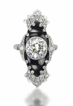 ART DECO ONYX AND DIAMOND JEWELLERY. Comprising a bracelet centering upon an onyx plaque inset with an oval-shaped diamond collet and extending a diamond-set openwork bracelet, a brooch and a ring en suite, 1920s. [Ring]