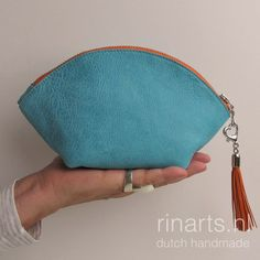 Turquoise leather zipper pouch with detachable orange tassel