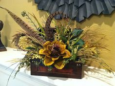 Smaller arrangement made in a two-tone brown wood trunk with a hinged lid accented with gold nailheads. Features a large dried magnolia flower,