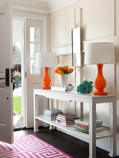 Add pops of colour to your entryway with bright lamps, rug and stacks of books. Add drawers to the console table for extra storage