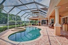 This golf course home for sale includes a large meandering pool and heated spa surrounded with a large brick-pavered pool deck.