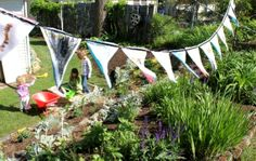 How to make simple garden wish flags with kids using fabric crayons and fabric. Draw and write your wishes on the fabric bunting then hang in the garden!