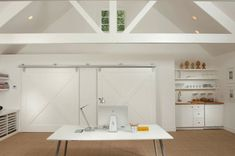 Stunning guest house office with vaulted, white beamed ceilings and sliding barn doors concealing storage.