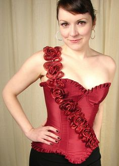 Rosey Floral Corset Top:This is a beautiful floral corset top. It is a red burgandy color and features flexible boning all the way around, a ruffle trim at the top and bottom, a diagonal row of what looks like organza flowers across the front going up to an adjustable shoulder strap, a side hook and eye closure with two rows for better sizing... $40.00