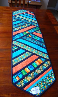 Wonderful table runner in a beautiful stain glass pattern with black accent. It is sure to make a stunning addition to your dining able kitchen table, coffee table, kitchen island, credenza, sideboard or bed.l table runner is 54 in. x 16 in. Patchwork Table Runner, Table Runner And Placemats, Table Runner Pattern, Quilted Table Runners, Coffee Table Runner, Plus Forte Table Matelassés, Halloween Table Runners, Place Mats Quilted, Quilted Table Toppers