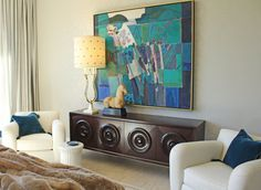 Creating a Balance: Because the bed is bursting with vibrant colors and patterns, I like that Sean kept the other side of the room fairly simple. The large-scale piece of abstract art strikes the perfect balance.