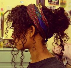 natural curls pulled up into a bandanna bun hairstyle