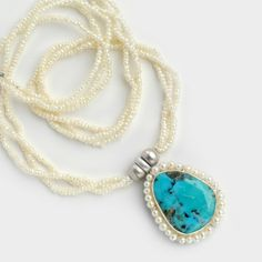Pearl necklace with oval turquoise stone surrounded by white pearls.