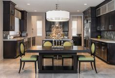 The beautiful dark wood cabinetry in this clean-lined kitchen is complimented by the vertical mosaic glass backsplash tile, oversized drum chandelier.  Chairs and barstools in energetic lime green.