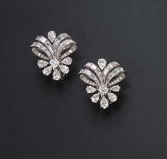 A PAIR OF DIAMOND EAR CLIPS Each designed as circular and baguette-cut diamond stylized ribbons, gathered by a circular and pear-shaped diamond demi-floret motif, mounted in platinum. Would guess circa 1950s-1960s.