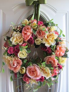 A beautiful wreath of pinks, rose, peach, creme yellows with greenery fillers that add a garden feel.