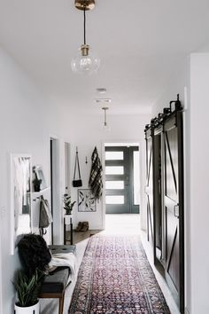 Love this modern hallway design! Get 4 tips for choosing hallway lighting, and update your outdated light fixtures today! These brass pendant lights with glass shades from Crate and Barrel are gorgeous in this white hallway! Love the way these brass pendants look with the maroon rug, dark hallway doors, and low hanging artwork. #hallway #lighting #fixtures #pendant White Hallway, Modern Hallway, White Walls, Glass Pendant Light, Brass Pendant, Pendant Lights, Hallway Lighting, Cool Lighting, Hall Tiles