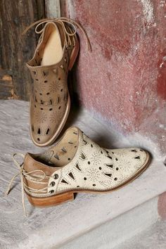 """Tooled stars and open cutwork bring texture and surprise to these leather booties, laced up the back for a feminine flourish. 1-1/4"""" heel."""
