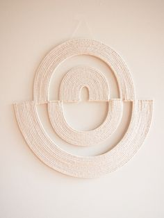 This piece is part of a new collection of works called White on White.This collection will explore the fragility and strength of materials in unexpected ways.This collection will be available in 2016.This woven wall hanging was created with paper and cotton rope, using a basket coiling technique.