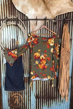 - Olive floral off the shoulder top - Longsleeve with slightly flowy bell cuff - Sets just below the top of the shoulder - Wide band elastic edge at back to keep from sliding down - Slight hi-lo hem w