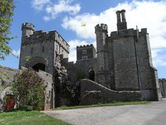 Powderham Castle, Devon, view of the Victorian entrance tower (left) and causeway from south-west