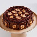 Bolo Chocolate com Nozes feito com: Massa de nozes recheada e coberta com brigadeiro e pedaços de Nozes.