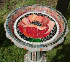 Poppy BirdbathSmall mosaic birdbath with a large poppy center.  The base has mosaic detail up the pedestal and around the foot section.  Can be done in a custom design and colors