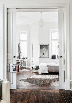 Mattorna i sovrummet är köpta under en resa i Sydafrika, golvlampan I burspråket, klassikern Toio från Flos. Fotografi på väggen, Andy Warhol från Fotografiska.