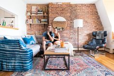 Max Shay, Emily Billings, and our cat, Snowboots in our 655 square feet South End  Boston home we've been renting for five months. The majority of walls in the row house are brick, a characteristic that has appeared in a few of our apartments in the city.
