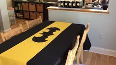 Batman birthday party. Bought a plastic table cloth and cut out the batman logo. Cost $1 as I had a black table cloth. This could be done with any logo.