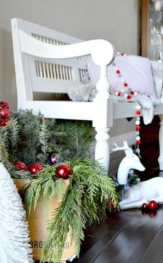 Kristin's pom-pom garland is a simple and easy DIY that makes a plain white bench stand out. She also filled up a pail with leftover tree trimmings, topping it off with a couple ornaments.   See the full house tour at My Uncommon Slice of Suburbia »  - GoodHousekeeping.com