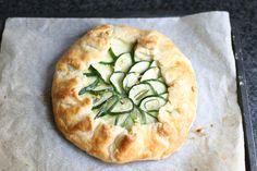 Besprenkel courgetteschijfjes met zout, laat minstens halfuur uitlekken. Dep droog. Haal rozemarijnblaadjes van paar takjes, meng met 1,5 el olijfolie en 1 geperst teentje look. Meng 150ml risotto met 150ml parmezaan, half bolletje mozzarella & 1 tl van het look-rozemarijnoliemengsel + pezo. Smeer mengsel uit over deeg, maar laat boord van 5 cm vrij. Schik courgetteschijfjes. Besprenkel met rest van de olie. Vouw buitenrand naar binnen. Borstel korst met eierdooier. Bak 30 à 40' op 200°.