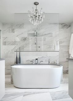 Spa-like marble clad bathroom is equipped with an Azzura bathtub placed on marble floor tiles beneath a crystal chandelier and against a freestanding gray quartz tub deck.